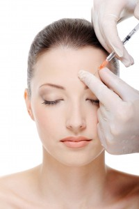 giving an injection in the eyebrow on the female face - white background